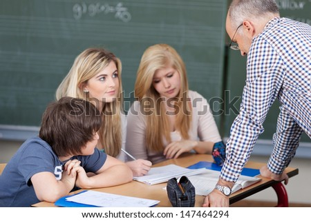Male teacher giving a lesson to two young girls and a boy seated at a desk - stock photo