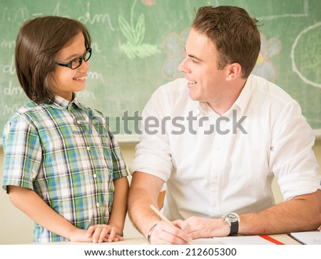 Male teacher helping kids in classroom during the class - stock photo
