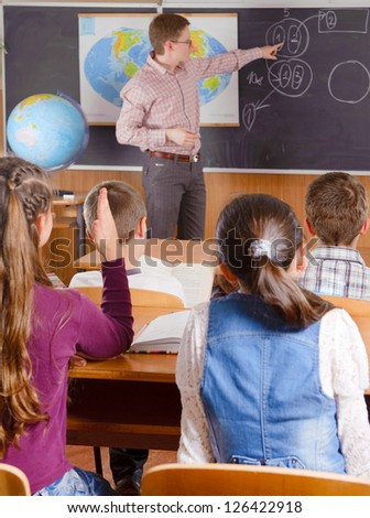 Male teacher in front of elementary age schoolchildren. - stock photo