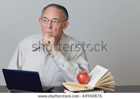 Male teacher in some serious thought.  Sitting in front of computer with books and apple on side of table.
