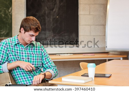 Male teacher looking at his watch - stock photo