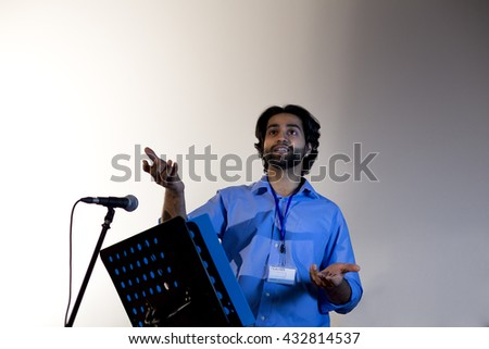 Male teacher making a speech in a lecture hall. He is standing at the podium and smiling to the crowd.