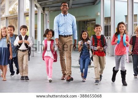 Male teacher walking in corridor with elementary school kids - stock photo