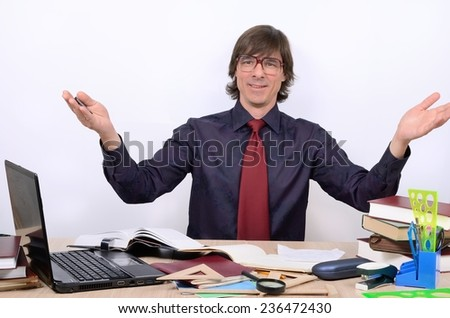 Male teacher with glasses at the table affably threw his arms - stock photo