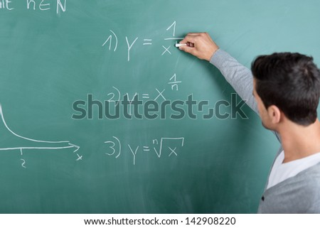 Male teacher with his back to the camera writing a mathematical formula on the blackboard in a classroom while teaching a class