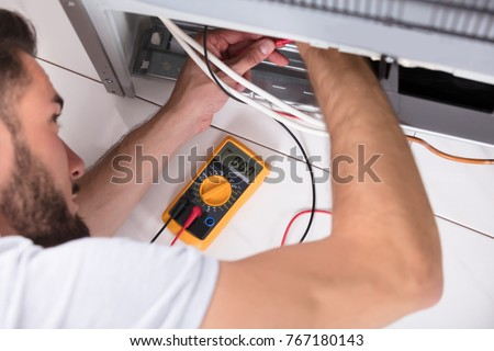 Male Technician Examining Refrigerator With Digital Multimeter