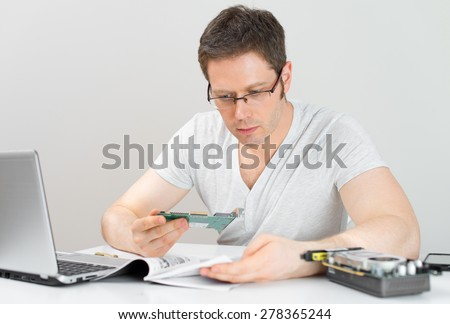 Male technician reading manual at his workplace. - stock photo