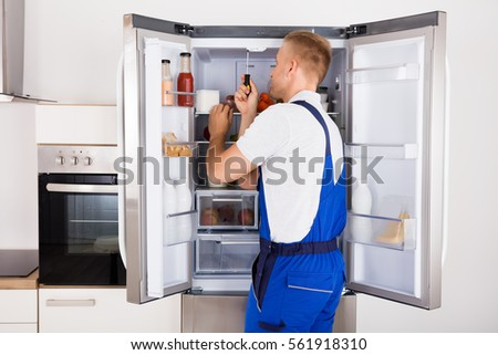 Male Technician Repairing Broken Refrigerator Appliance With Screwdriver