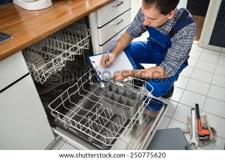 Male Technician Sitting Near Dishwasher Writing On Clipboard In Kitchen - stock photo