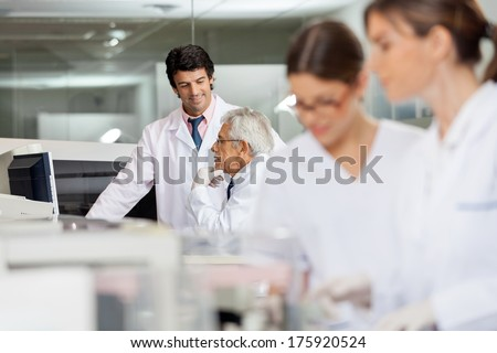 Male technicians discussing in lab with female colleagues working in foreground - stock photo