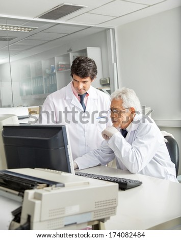 Male technicians discussing over computer in laboratory - stock photo
