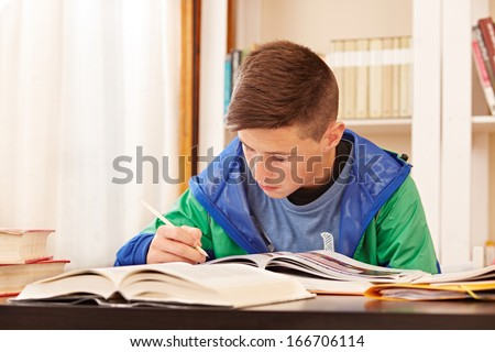 Male teenager concentrated doing homework in a desk - stock photo