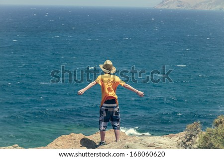 male teenager standing on a cliff with blue ocean in background. - stock photo