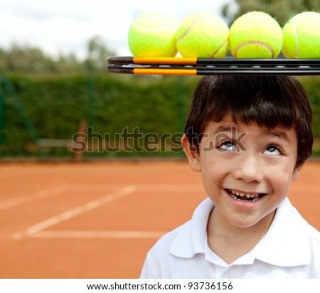 Male tennis player a racket and balls on top of his head - stock photo
