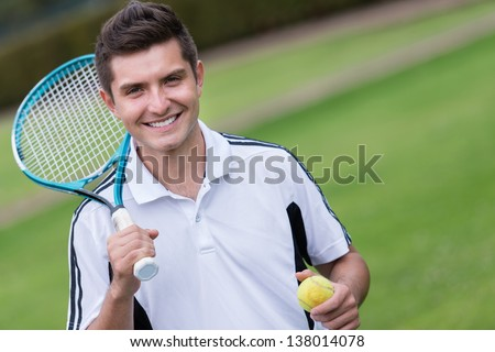 Male tennis player at the court looking happy - stock photo