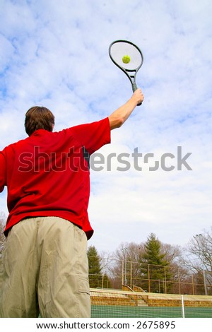 Male tennis player hitting the ball from above