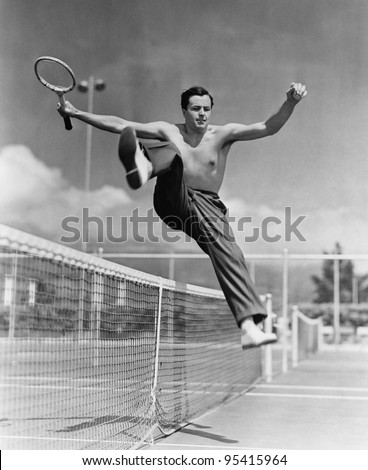 Male tennis player jumping over net - stock photo