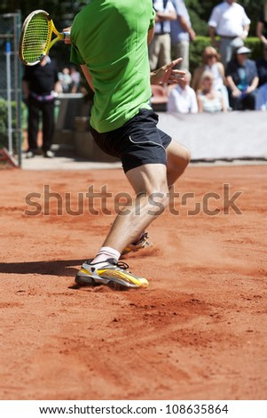 Male tennis player lunging for the ball - stock photo