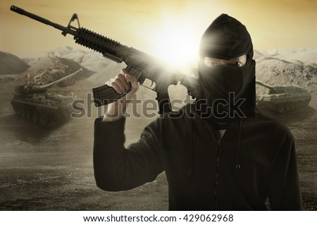 Male terrorist wearing mask and holding a machine gun with military vehicle background