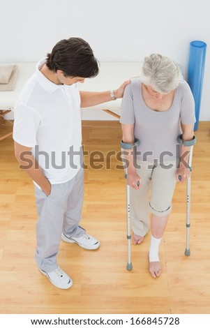 Male therapist assisting disabled senior patient to walk in the gym at hospital - stock photo