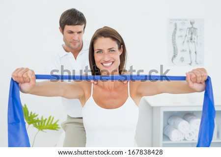 Male therapist assisting young woman with exercises in the medical office - stock photo