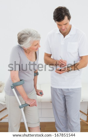 Male therapist discussing reports with a disabled senior patient in the gym at hospital - stock photo