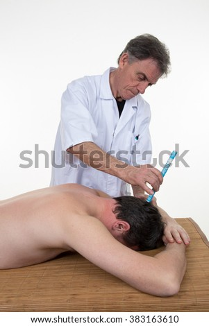 Male therapist in chinese medicine working on the back of a  man - stock photo