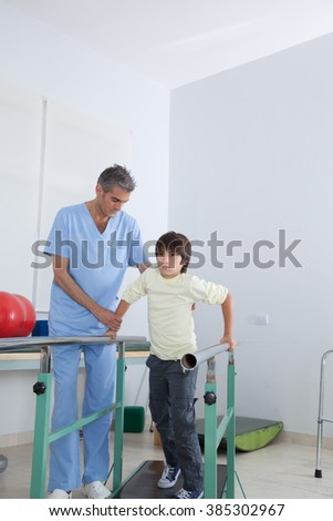 Male therapist with boy in parallel bars