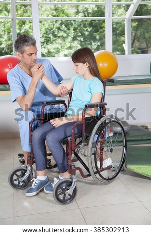 Male therapist with girl in wheelchair