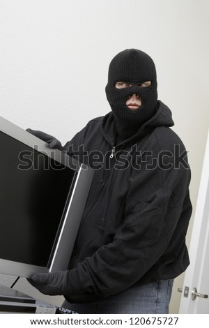 Male thief in mask stealing television from house