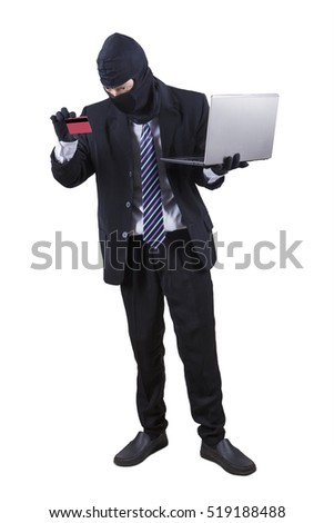 Male thief stealing money with a laptop computer and credit card, isolated on white background