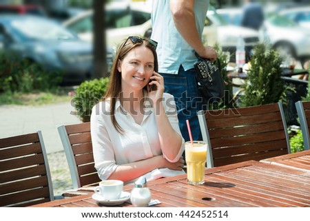 Male Thief Stealing Purse Of A Young Woman Using Mobile Phone - stock photo
