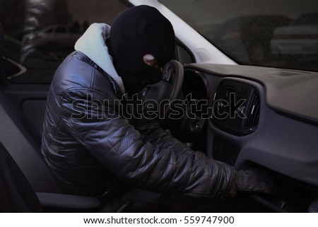 Male thief stealing valuables from car