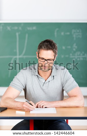 Male thoughtful teacher checking examination papers at bench in classroom - stock photo