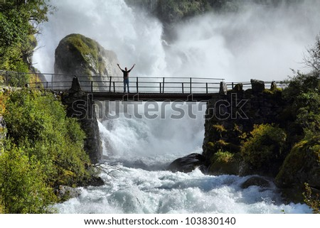 Male tourist above an extremely powerful waterfall in Briksdalen valley, Jostedalsbreen National Park in Norway. - stock photo