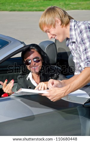 Male tourist asking female driver about direction - stock photo