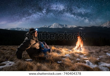 Male tourist have a rest in the mountains at night. Guy with a headlamp sitting near campfire under beautiful night sky full of stars and milky way, and enjoying night scene