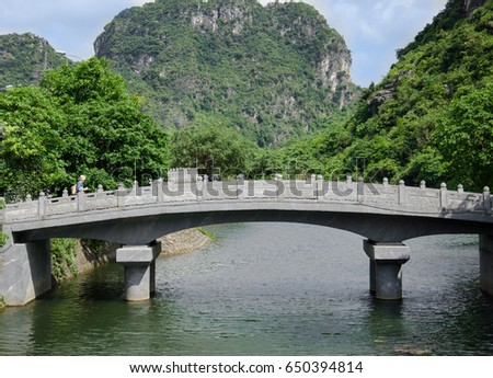 Male tourist on the stone bridge with river and mountain in Vietnam.