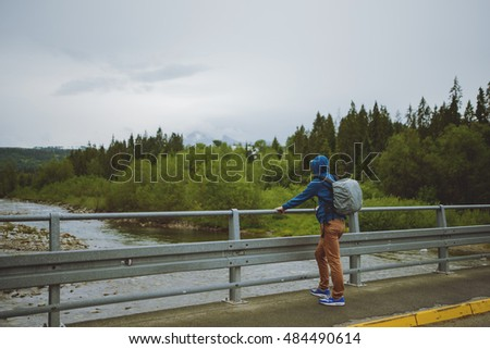 male tourist standing beside the mountain river.