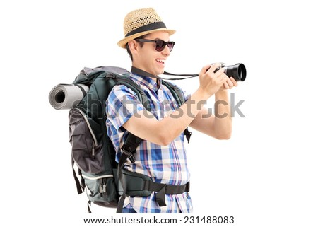 Male tourist taking a picture with a camera isolated on white background