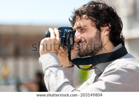 Male tourist taking picture in the city - stock photo