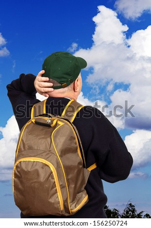 male tourist with a backpack and a baseball cap looks up at the sky with clouds. - stock photo