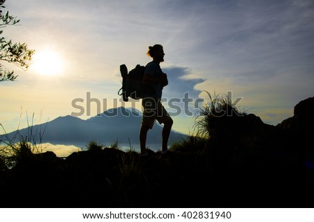 Male tourist with a backpack on his back rises in the mountains. Stock image.