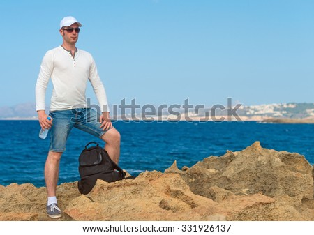 Male tourist with backpack standing near the sea. Place for your text.