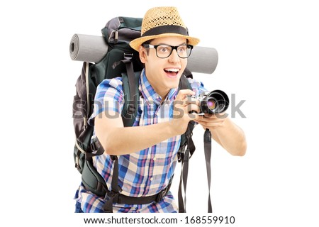 Male tourist with backpack taking a picture with the camera isolated on white background