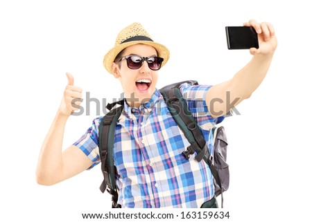 Male tourist with backpack taking pictures of himselves with mobile phone and giving thumb up isolated on white background