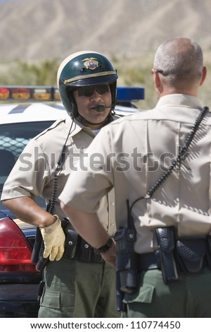 Male traffic officers having conversation - stock photo