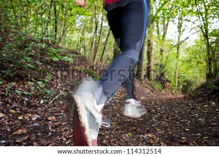 Male trail runner running in the forest on a trail.Close-up on running shoes. Summer season. Slight blur in runner to show motion. Horizontal composition. - stock photo