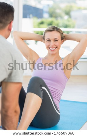 Male trainer assisting fit woman in doing sits up at gym - stock photo