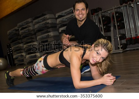 Male trainer assisting pretty woman with push ups in fitness studio - stock photo